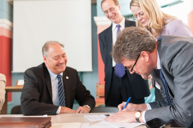 John Dalley, Chief Financial Officer of Scotmid, signs the paperwork with John Mills, Chief Executive Officer of Penrith Co-operative.
