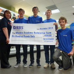 The team accepts their cheque from Scotmid.