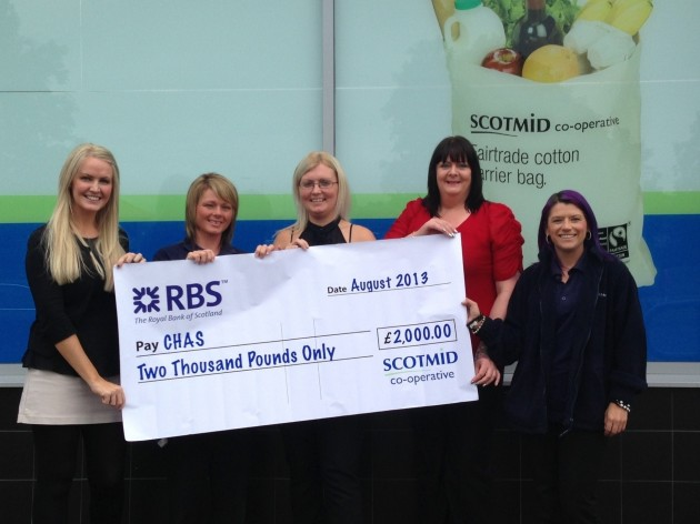 Grace Wilson from CHAS accepts a cheque from the Scotmid Alexandria team.