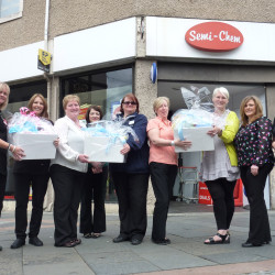 Staff from Scotmid and Semichem hand over baby goods to Hillhouse volunteers